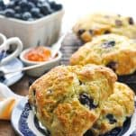 Front shot of blueberry scones on a plate with fresh blueberries in the background