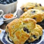 Two blueberry scones on a plate with jam and blueberries in the background