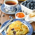 Blueberry scone on a blue and white plate with apricot jam in the background