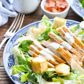 Sliced chicken breast on top of caesar salad