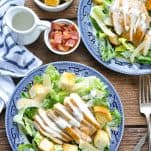 Overhead image of two plates of Chicken Caesar Salad on a wooden table