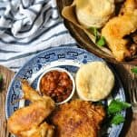 Crispy fried chicken recipe on a wooden table with a blue and white striped towel nearby