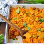 Front shot of a wooden spoon scooping up easy Dorito casserole from a white dish
