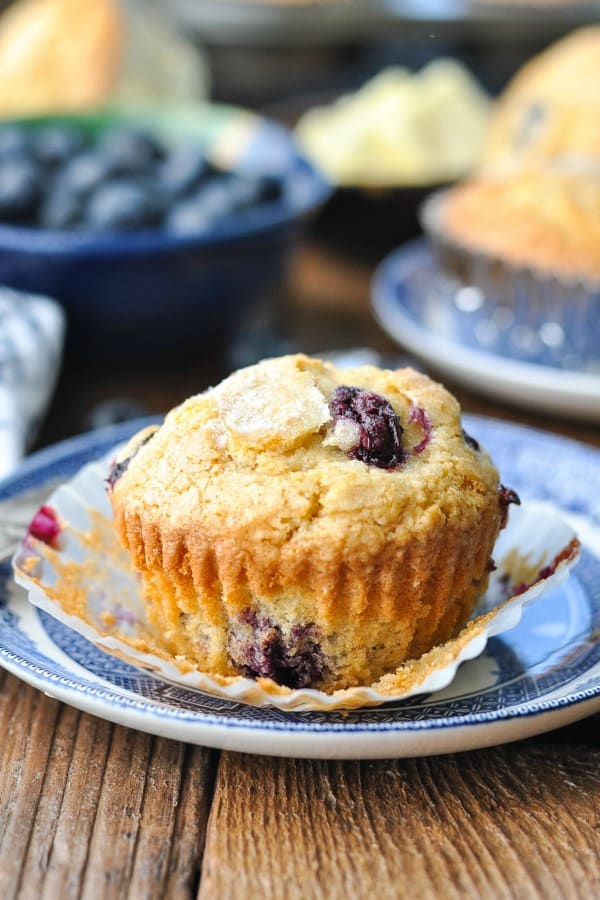 Front shot of a homemade blueberry muffin on a blue and white plate