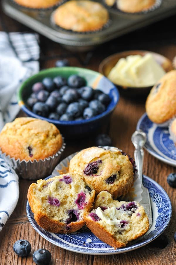 Shot of blueberry muffins on a plate with one cut open and butter spread on half