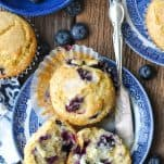 Overhead image of a plate with homemade blueberry muffins and a butter knife
