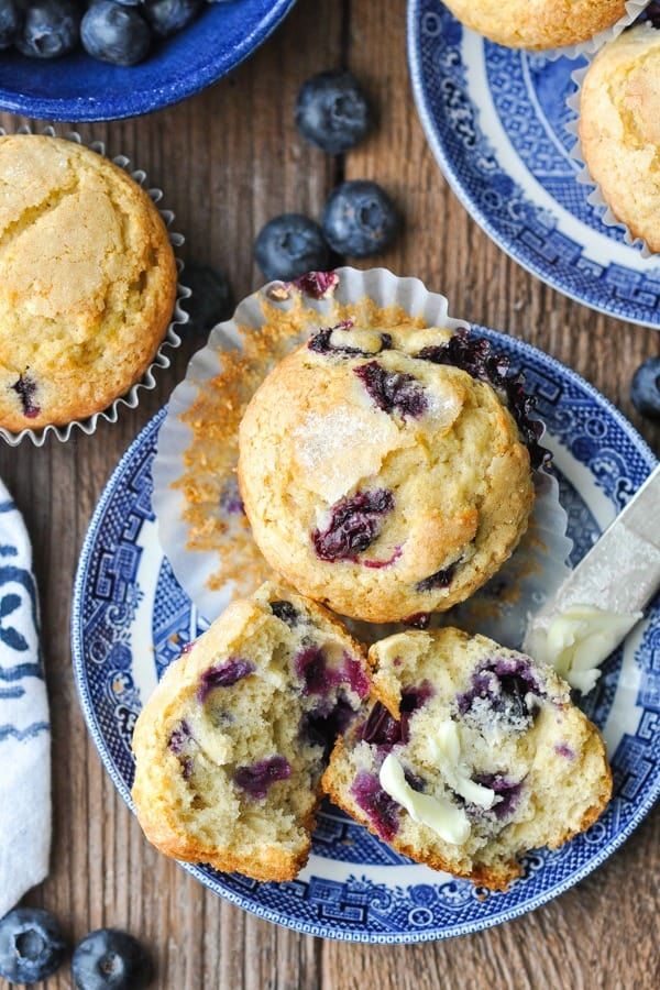 Close overhead shot of two easy blueberry muffins on a blue and white plate
