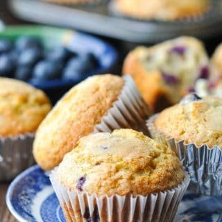 Front shot of three easy blueberry muffins on a blue and white serving plate with more muffins and fresh berries in the background