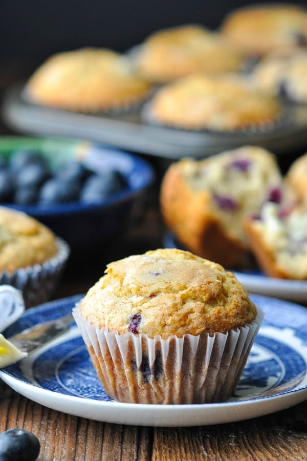 A homemade bakery style easy blueberry muffin on a blue an white plate