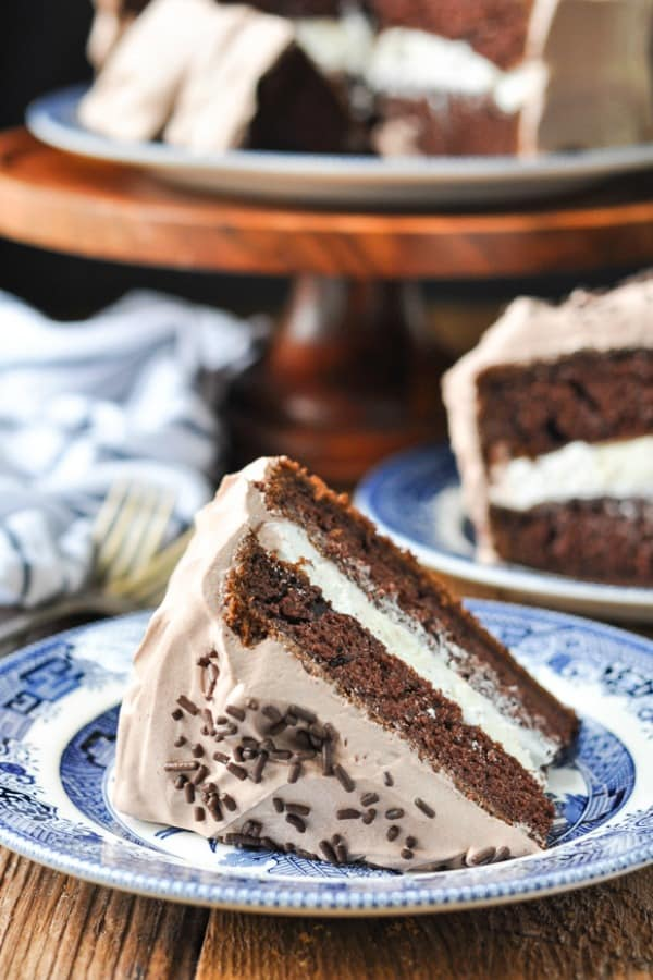 Close up front shot of a slice of easy chocolate cake with cake stand in the background