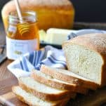 Front shot of a loaf of sliced homemade white bread on a cutting board with jar of honey and butter in the background