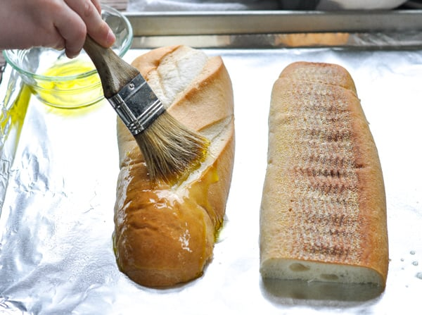 Brushing french bread with olive oil