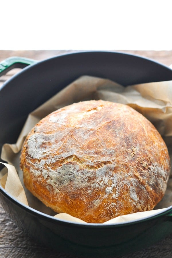 Close up front shot of a loaf of no knead bread on parchment paper in a dutch oven