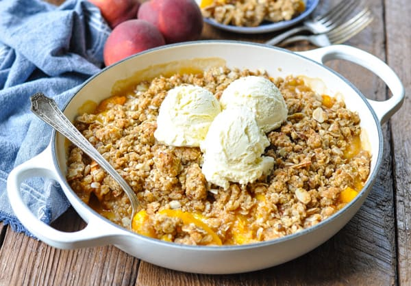 Horizontal shot of baked warm peach crisp with vanilla ice cream on top