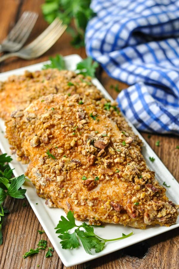 Overhead shot of a white rectangular serving tray full of pecan crusted chicken breast