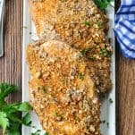 Overhead shot of baked pecan crusted chicken on a white rectangular serving tray