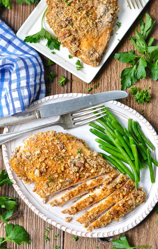 Overhead image of a plate of pecan crusted chicken breast with a side of green beans