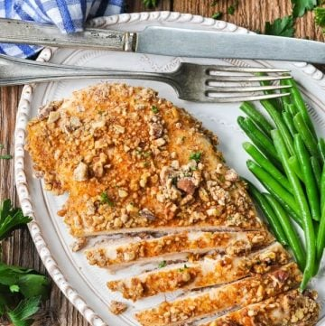 Close overhead image of a sliced pecan chicken breast on a plate with green beans