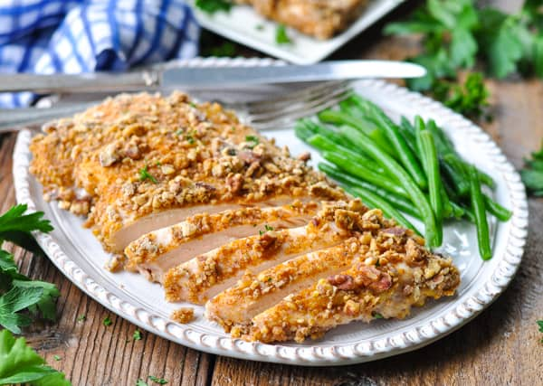 Horizontal shot of a large pecan crusted chicken breast sliced on a white plate