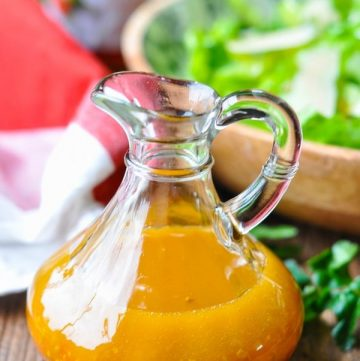 Glass bottle of homemade pepper jelly vinaigrette on a wooden table with salad in the background