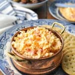 Front shot of homemade pimento cheese recipe in a copper bowl with olives in the background