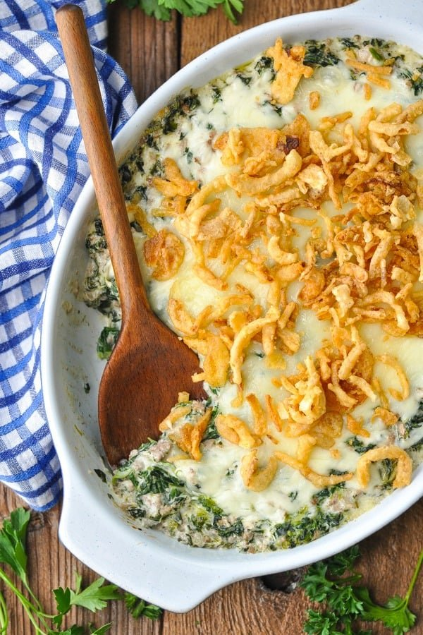 Overhead image of spinach casserole with ground beef and a blue and white check napkin nearby