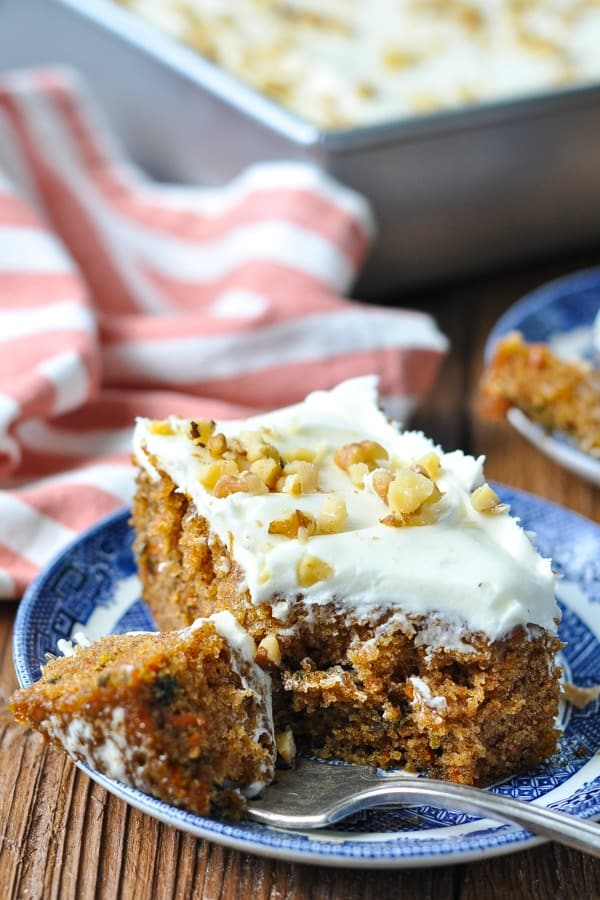 Close up front shot of a slice of carrot cake with a bite on a fork