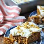 Two slices of the best carrot cake recipe on blue and white serving plates with an orange striped towel nearby