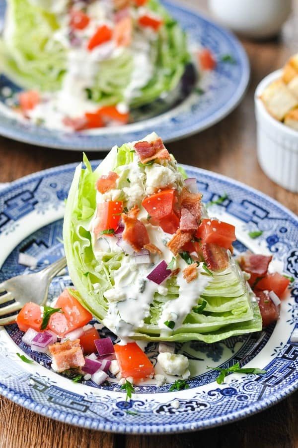 Iceberg wedge salad on a plate with bacon, tomatoes and ranch on top