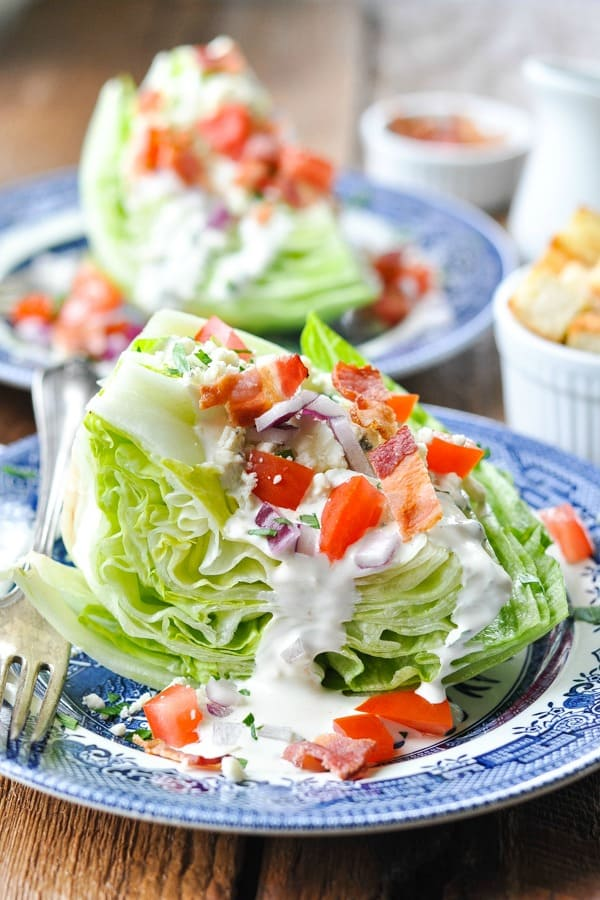 Classic Wedge Salad recipe with Ranch on a blue and white plate