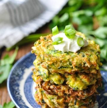 Four zucchini fritters stacked on a blue and white plate