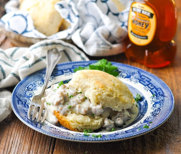 Square image of buttermilk biscuits and gravy on a wooden table with a bottle of honey in the background