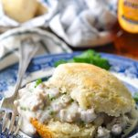 Homemade biscuits and sausage gravy garnished with parsley on a blue and white plate