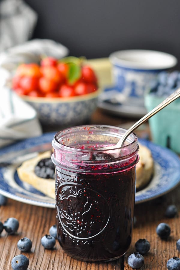 Side shot of a spoon in an open jar of blueberry jam with fruit coffee and toast in the background