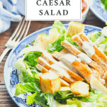 Front shot of a bowl of chicken caesar salad with text box title at top