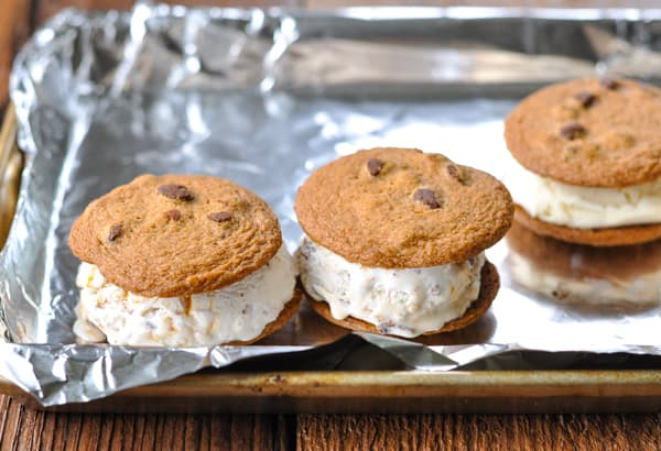 Chocolate chip cookie ice cream sandwiches on a sheet pan