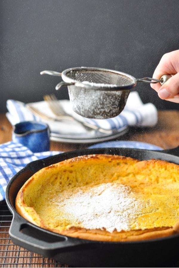 Sprinkling a Dutch Baby Pancake with powdered sugar