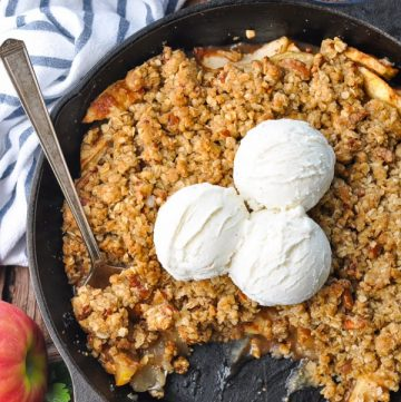 Close overhead shot of an easy apple crisp baked in a cast iron skillet with vanilla ice cream on top