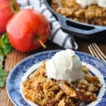 Front shot of apple crisp served on a blue and white plate with scoop of ice cream on top