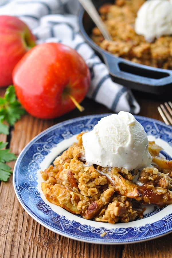 Close up side shot of a serving of easy apple crisp on a small blue and white plate on a wooden table