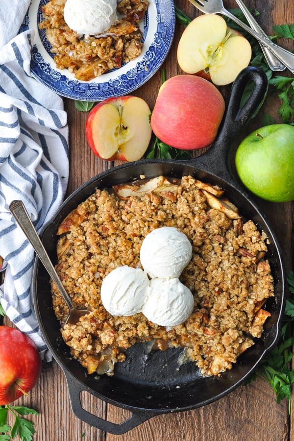 Overhead shot of apple crisp on a wooden table surrounded by red and green apples