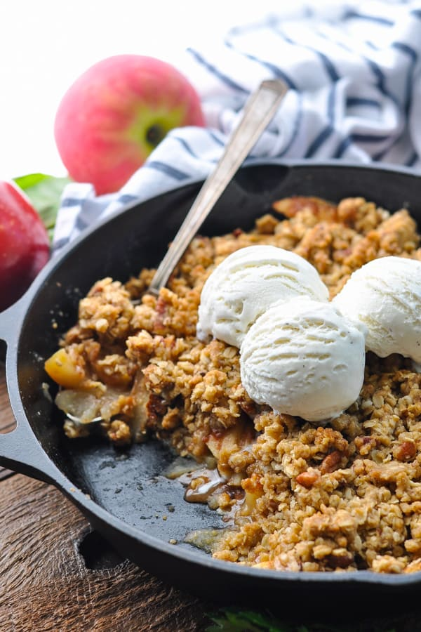 Close up front shot of a silver spoon scooping apple crisp from a cast iron skillet
