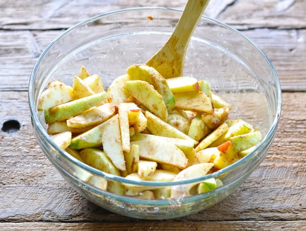 Filling for apple crisp in a glass mixing bowl with wooden spoon