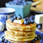 Stack of fluffy pancakes on a blue and white plate with butter blueberries and syrup on top