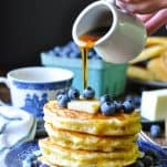 Pouring syrup from a white pitcher over a stack of homemade buttermilk pancakes