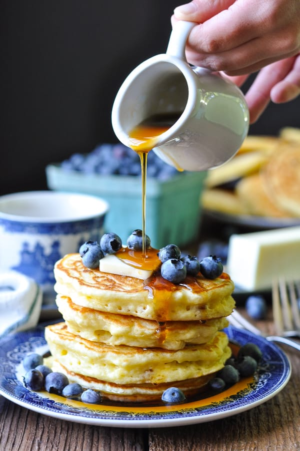Front shot of small hands pouring syrup on a plate of fluffy buttermilk pancakes