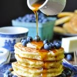 A plate piled high with blueberries and fluffy pancakes while syrup is poured over top