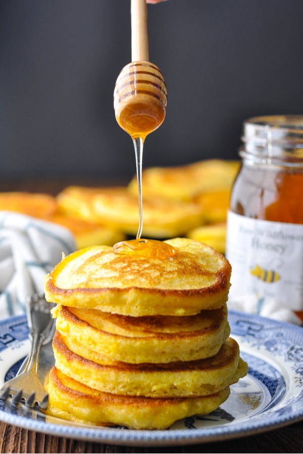 Front shot of honey drizzling on top of a stack of hoe cakes