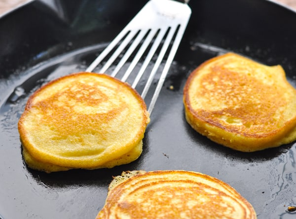 Horizontal shot of cornmeal griddle cakes in a cast iron skillet