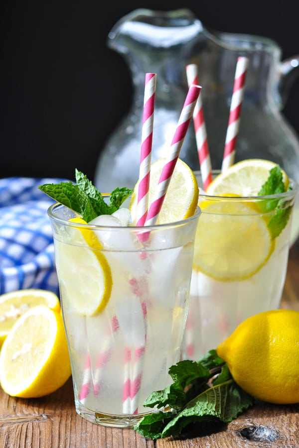 Two glasses of homemade lemonade with pink and white striped straws in each glass